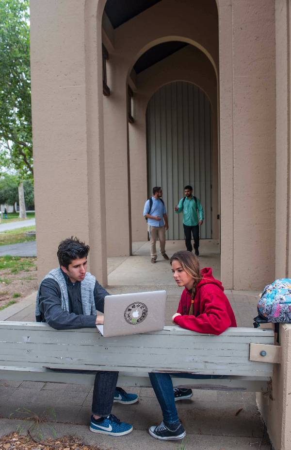 Students at a bench with a laptop